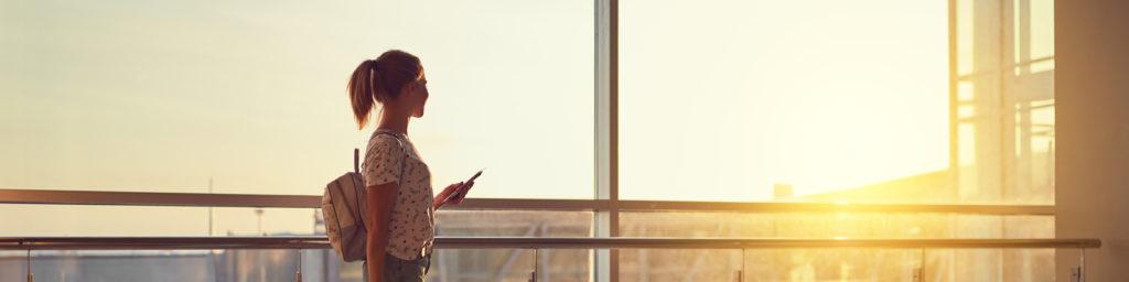pasajero mirando por la ventana de un aeropuerto